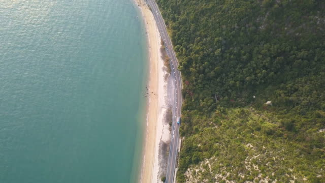 aerial view of a road running between a mountain and the ocean - aerial beach stock videos & royalty-free footage