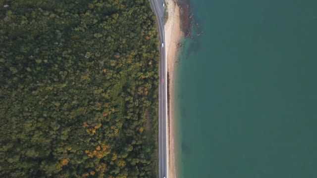 aerial view of a road running between a mountain and the ocean - semplicità video stock e b–roll