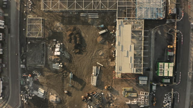 Aerial view of a school building site with various materials and vehicles shot overhead on a cold winters morning with a drone