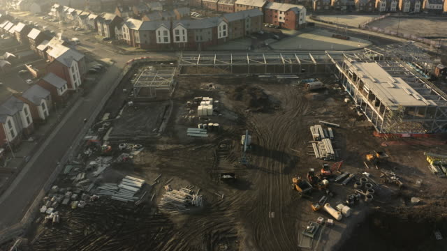 aerial view of a school building site with various materials and vehicles shot overhead on a cold winters morning with a drone - osiedle mieszkaniowe filmów i materiałów b-roll