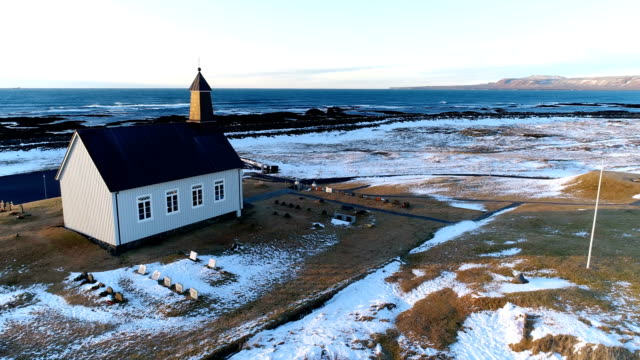 Aerial view of a simple church alone in Iceland, near the Atlantic Ocean. There is snow and ice around the evangelical church, under the sunset.