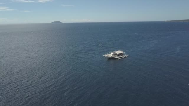 aerial view of a small tourist boat docked in the blue calm ocean in summer day. - passenger craft stock videos & royalty-free footage