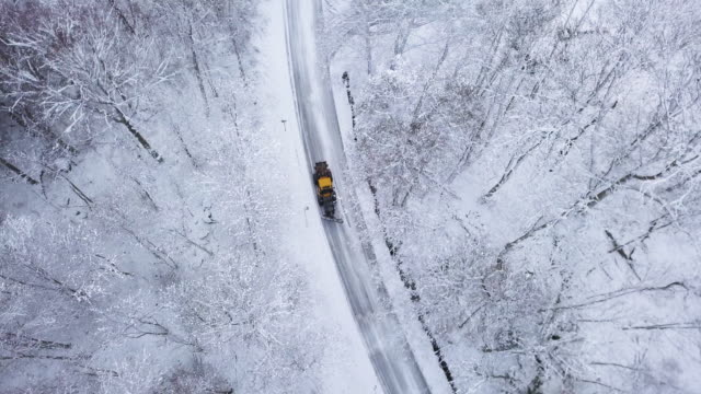 Aerial View of a Snowplow driving Through Snow A snow covered road in a winter woodland in Scandinavia. Shot from directly above in 4K resolution. plow stock videos & royalty-free footage