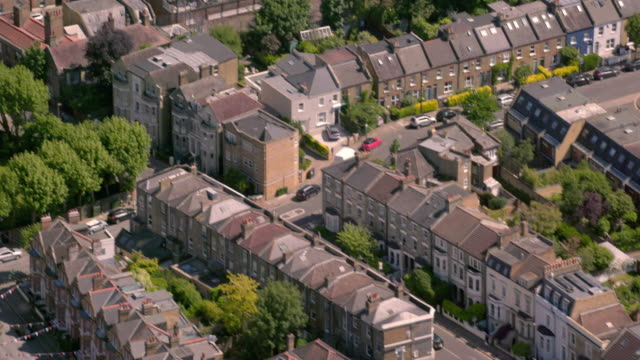 Aerial View of a Street in Outer London, UK. 4K An aerial view of a typical residential street in the suburbs of London, UK, showing Victorian era terraced houses and modern tower blocks. Filmed from a helicopter in full 4K in lovely sunshine. 19th century style stock videos & royalty-free footage