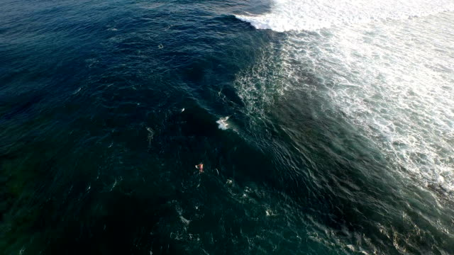 Aerial view of a surfer paddling out to the lineup through the channel video