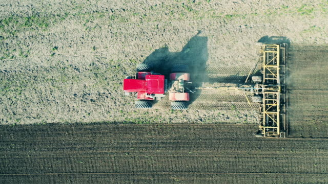 Aerial view of a tractor, working on a field with soil. Aerial view of a tractor, working on a field with soil. 4K agricultural occupation stock videos & royalty-free footage