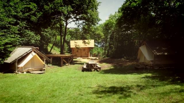 森の中にある夏のキャンプでの伝統的な木造住宅の空撮 - キャンプ点の映像素材/bロール