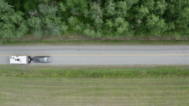 aerial view of a truck pulling a camper trailer on country road - caravan stock videos & royalty-free footage
