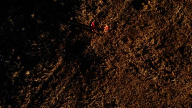 vista aerea di un viaggiatore di due ragazze con zaini e telecamere passeggia tra le colline tra le rocce epiche in montagna - dorso umano video stock e b–roll