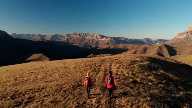 luftaufnahme einer zwei mädchen reisenden mit rucksäcken und kameras schlendern durch die hügel zwischen den epischen felsen - hochplateau stock-videos und b-roll-filmmaterial
