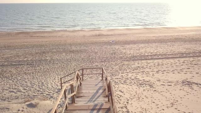 flygfoto över en gångväg på stranden vid solnedgången. video skott i sabaudia, en vacker vilda strand på västkusten i centrala italien. - idyllisk bildbanksvideor och videomaterial från bakom kulisserna