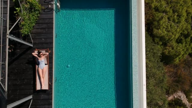 aerial view of a women sunbathing by the infinity pool - affluent lifestyles stock videos & royalty-free footage