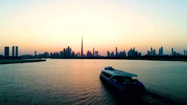 aerial view of a yacht in the bay of dubai during sunset, u.a.e. - dubai video stock e b–roll