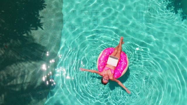 flyg foto av en ung brunett kvinna simma på en uppblåsbar stor munk med en bärbar dator i en transparent turkos pool - inflatable ring bildbanksvideor och videomaterial från bakom kulisserna