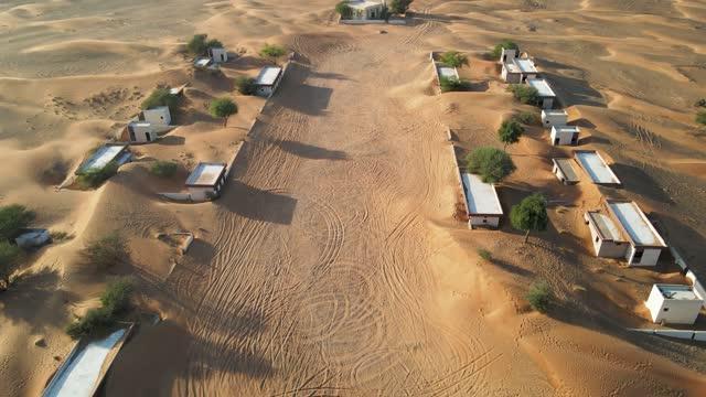 Aerial view of abandoned houses in the UAE desert near Dubai, overtaken by sand dunes