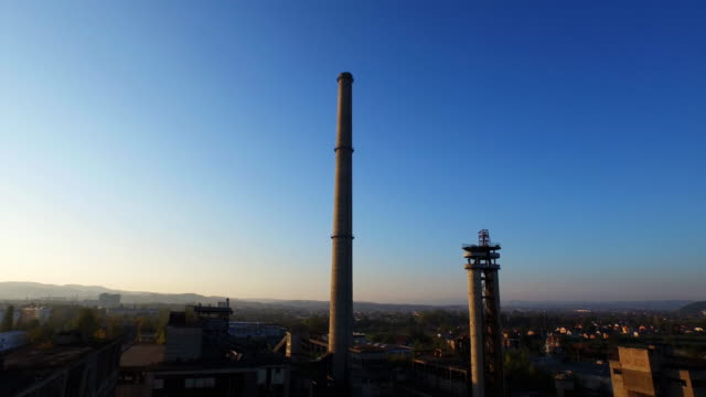 aerial view of abandoned industrial buildings and chimney at sunset - barile video stock e b–roll