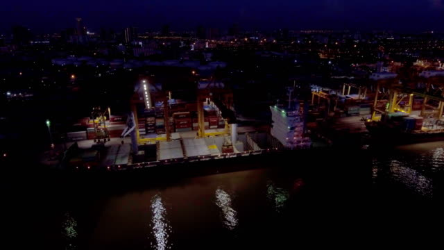 vídeos de stock e filmes b-roll de aerial view of aerial view of industrial and container ship logistic harbor at night, bangkok, thailand - drone shipyard night