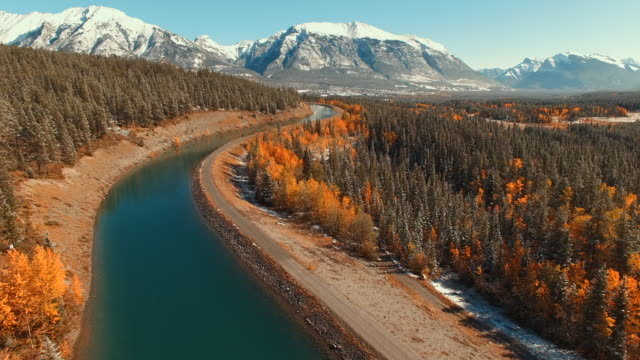 stockvideo's en b-roll-footage met luchtfoto van alpine rivier met sneeuw bedekte bergen in de verte - sneeuwkap