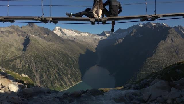vídeos de stock, filmes e b-roll de vista aérea dos alpes olhando para a fronteira da cordilheira da áustria e itália mostrando casal sentado em ponte de corda - tyrol state austria