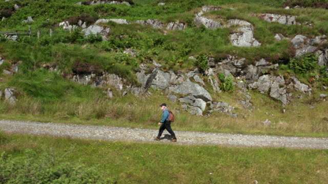 Aerial view of an active retired man walking on a dirt road in a remote part of south west Scotland. video