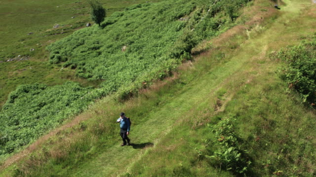 Aerial view of an active retired man walking on a disused railway line in a remote part of south west Scotland. video