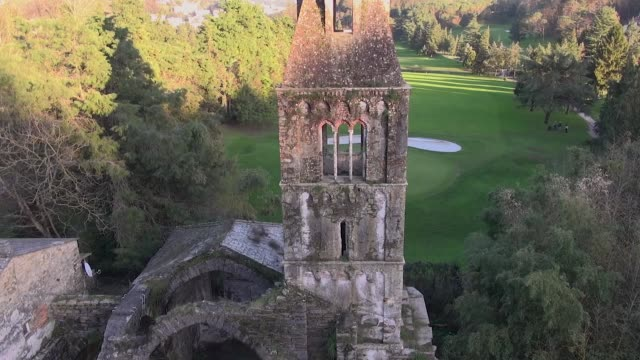 aerial view of an ancient abandoned church with golf green field on back video