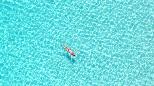 Aerial view of an attractive woman floating in crystal clear sea video