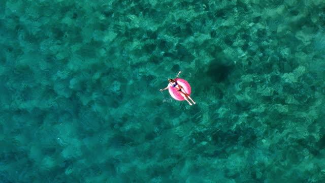 stockvideo's en b-roll-footage met luchtfoto van een aantrekkelijke vrouw drijvende - opblaasband