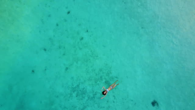 Aerial view of an attractive woman in a bikini floating in crystal clear sea. Pretty beatiful girl swimming in Indian ocean video