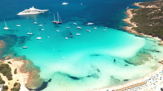 aerial view of an emerald and transparent mediterranean sea with a white beach and some yachts. gulf of the great pevero, costa smeralda, sardinia, italy. - sardegna video stock e b–roll