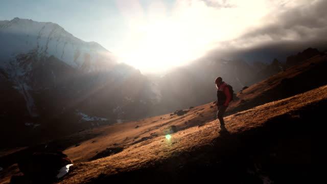 luftaufnahme einer epischen aufnahme eines mädchens, das am rande eines berges als silhouette in einem wunderschönen sonnenuntergang spazieren geht. silhouette eines mädchens in einem hut mit einem rucksack, der den berg hinunter auf einem berghang - niedrig stock-videos und b-roll-filmmaterial