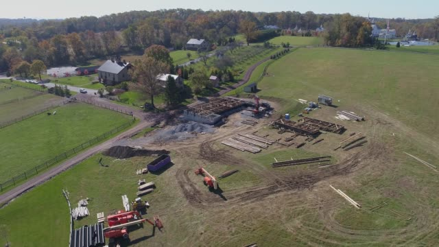 Aerial view of an old timber frame barn being rebuilt and restored drone circling construction site