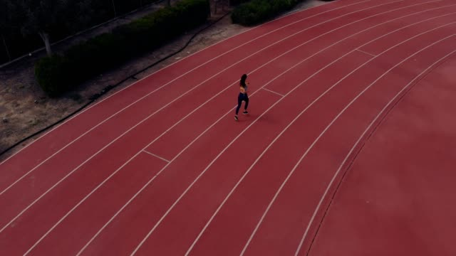 aerial view of athletic woman running on running track - track and field stock videos and b-roll footage