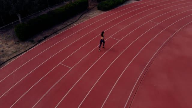 Vista aérea de mujer atlética corriendo en pista de atletismo - vídeo