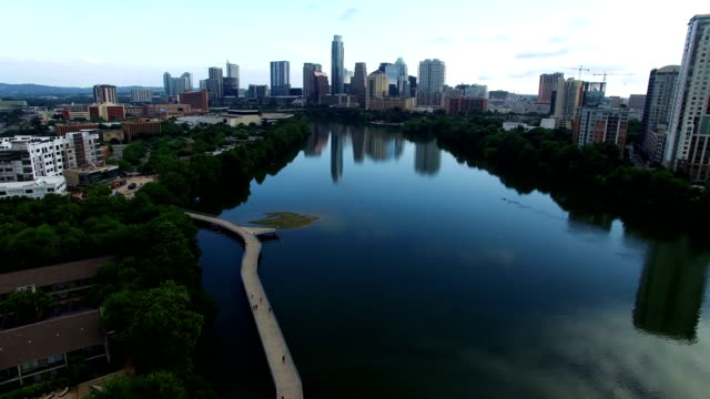 Aerial View of Austin , Texas , USA above Calm Blue Town Lake with Pedestrian Bridge modern curved route below and reflection of the Skyline in the background closer video