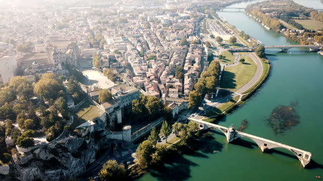 Aerial view of Avignon on bank of Rhone river Aerial view of Avignon on bank of Rhone river with Palais des Papes in sunny autumn day, France provence alpes cote d'azur stock videos & royalty-free footage