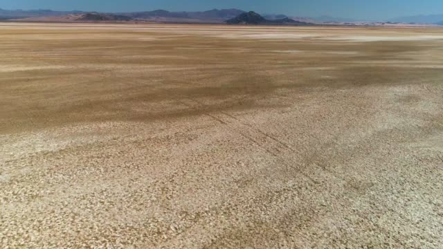 aerial view of backwards fast flight over desert salt flats This aerial video shows a fast in flight view going backwards over desert salt flats. salt flat stock videos & royalty-free footage