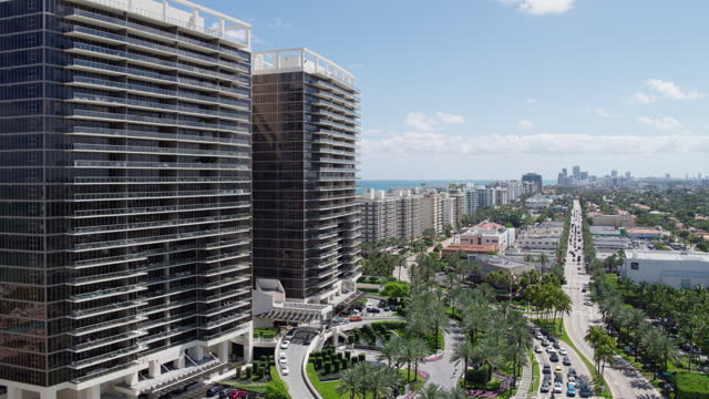 Aerial view of Bal Harbour along the street toward Surfside. Miami, Florida. Drone-made footage with backward camera motion. Aerial view of Bal Harbour and Surfside, Miami, Florida. 4K UHD B-Roll footage. ocean front properties stock videos & royalty-free footage