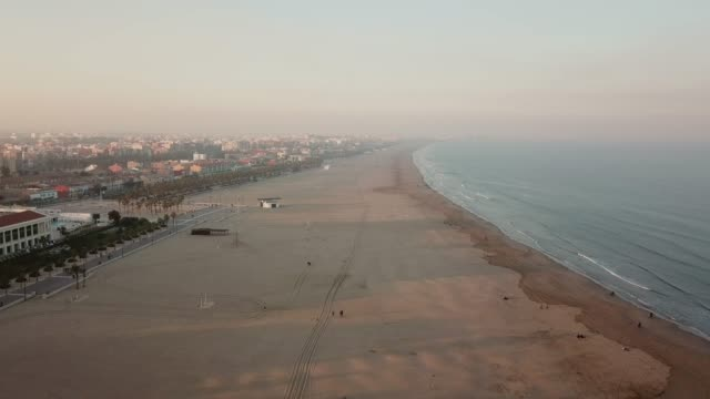 Aerial view of beach at sunset. Wide beach. Sand beach and sea view from above. View of the port city
