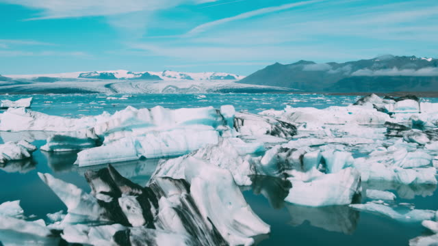 aerial view of beautiful blue glacier lagoon with giant icebergs in iceland - clima video stock e b–roll