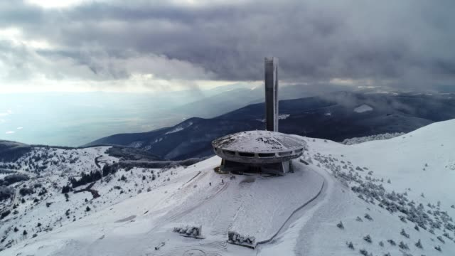 Aerial view of beautiful, dramatic, fast moving clouds over a mountain peak in the winter, science fiction mood, Buzludzha monument, UFO, the star rising above the fog, wanderlust Soviet monument in Bulgaria, historical and cultural architectural heritage, abandoned, partly destroyed, symbol of Comunism, majestic drone's flight view over the rising star that only shows up over the clouds cover. ghost icon stock videos & royalty-free footage