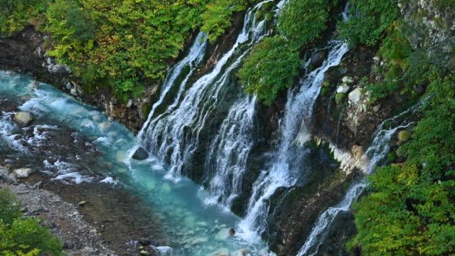 vídeos de stock e filmes b-roll de aerial view of beautiful shirahige waterfalls tumbling down into biei river in biei, hokkaido, japan - setembro
