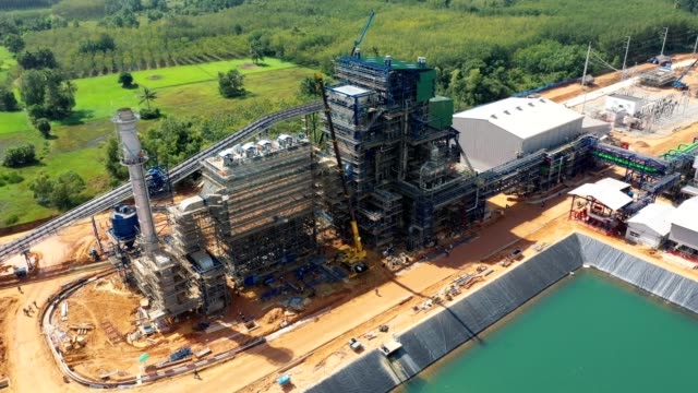 Aerial view of Biomass power plant with storage of wooden fuel against blue sky Aerial view of Biomass power plant with storage of wooden fuel against blue sky and raw water reservoir biomass renewable energy source stock videos & royalty-free footage