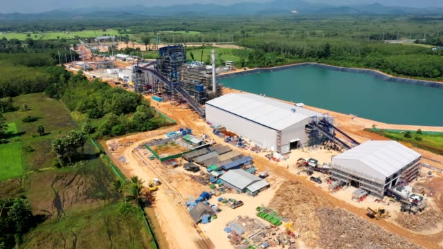 Aerial view of Biomass power plant with storage of wooden fuel against blue sky Aerial view of Biomass power plant with storage of wooden fuel against blue sky and raw water reservoir biofuel stock videos & royalty-free footage