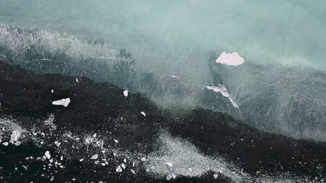 Aerial view of black sand ocean beach with icebergs in Iceland