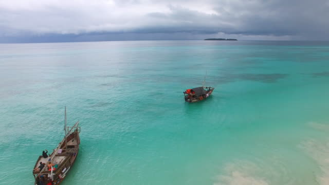 Aerial view of blue lagoon, people on boat, Nungwi, Zanzibar, Tanzania from above, Africa, Indian Ocean, 4k UHD Aerial view of blue lagoon, people on boat, Nungwi, Zanzibar, Tanzania from above, Africa, Indian Ocean, 4k UHD tanzania stock videos & royalty-free footage