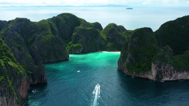 vídeos de stock e filmes b-roll de aerial view of boat sailing into phi phi le, phi phi islands, thailand - phuket