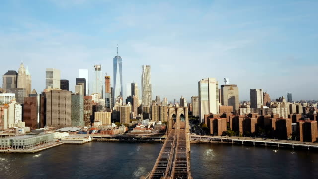Aerial view of Brooklyn bridge with American flag waving on the wind. Scenic view of East river, Manhattan in New York video