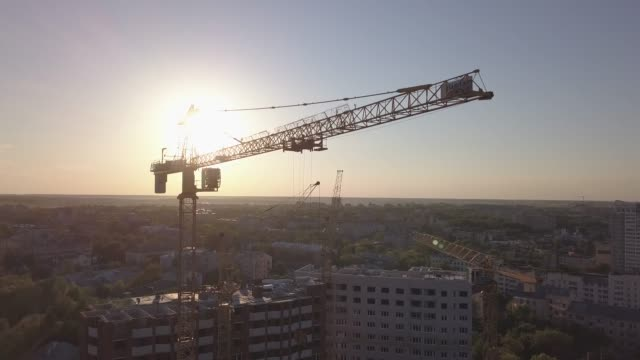 Aerial view of building cranes and buildings under construction. Silhouettes of cranes and construction site shot against the light.