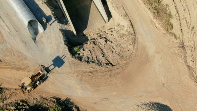 Aerial view of building new road. Flight above construction site, new highway